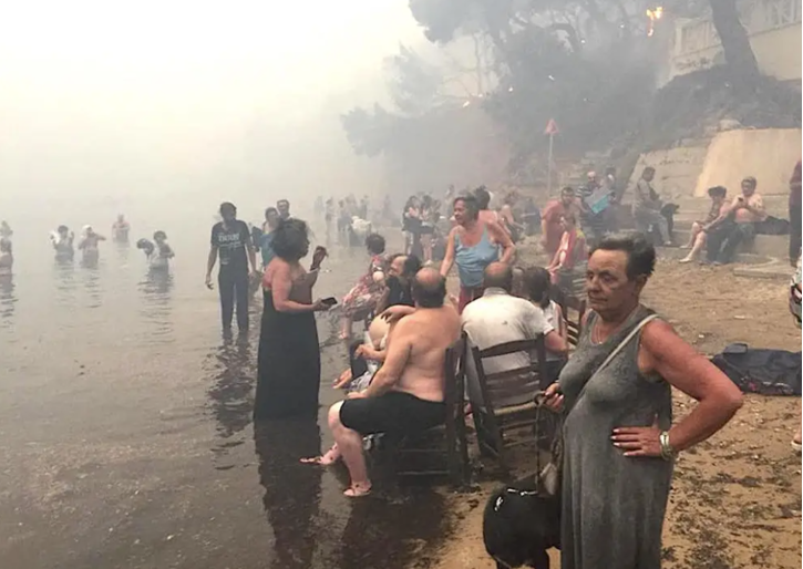 Figure 7: Residents of Mati awaiting rescue on the shore. (Source: https://www.insider.com/greece-wildfire-outside-athens-worst-since-2007-at-least-50-dead-2018-7)